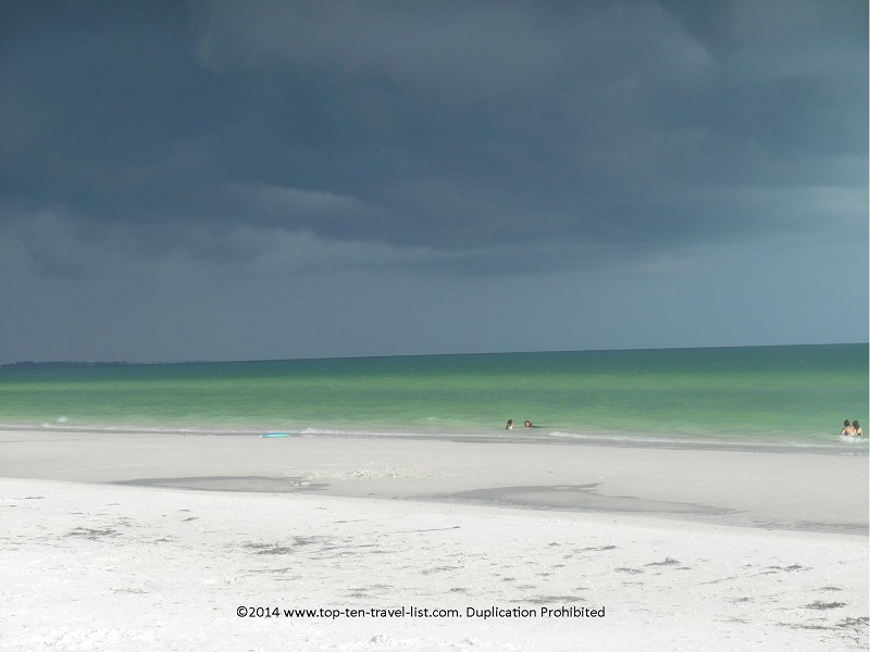 Greenish looking water against the dark storm clouds at Sarasota's Siesta Key Beach