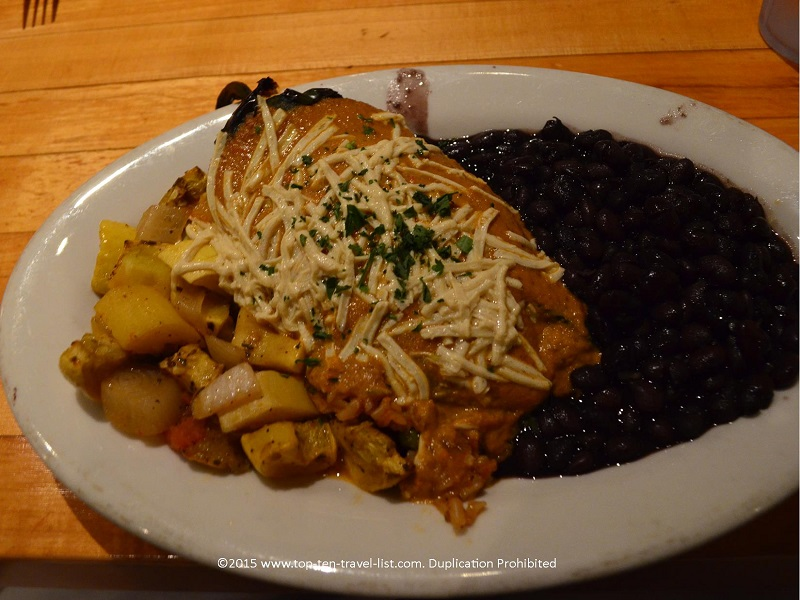 The Southwestern Stuffed Pepper (available gluten-free) is a poblano pepper filled with brown rice, corn, peas, tempeh, and cilantro, served with your choice of sauce and topped with regular or Daiya cheese. This tasty dish is served with black beans and sauteed squash.