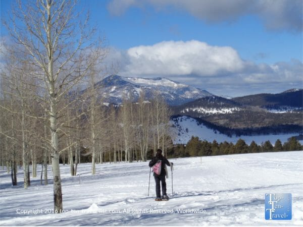 Snowshoeing with the gorgeous snow covered mountains in the backdrop at Arizona Snowbowl in Flagstaff, Arizona